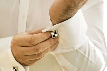 Cuff with cufflink being put on photo