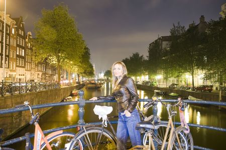 Pretty young woman standing next to retro bicycle in Amsterdam photo