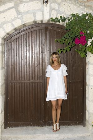 Young woman with long blond hair in a white dress standing in front of iron door.  photo