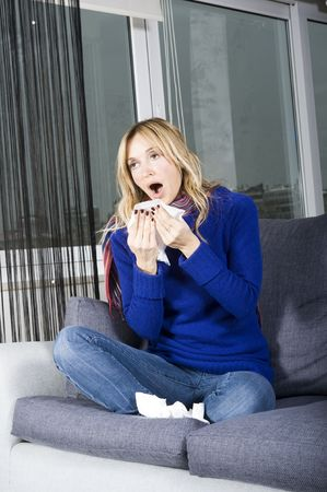 young woman blowing her nose with  photo
