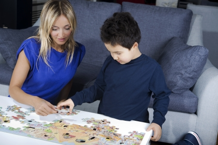 mother making a puzzle together with  her son  photo