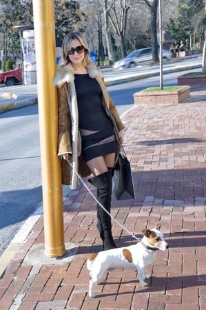 blond woman walking down the fashion district of a modern city with a jack russel photo