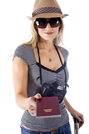 Smiling tourist woman with her camera, hat, and sunglasses showing her passport photo