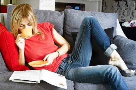 woman couch: beautiful blond woman having her morning coffee and reading her magazine