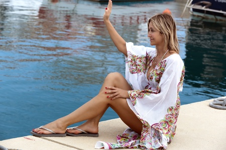 sexy blond woman waving at one of the boats at the marina photo