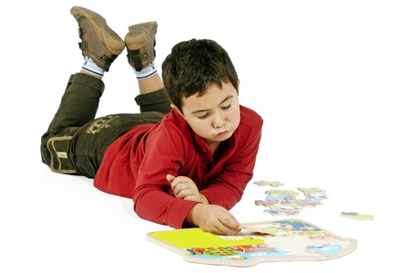 little boy lying on the floor making puzzles photo