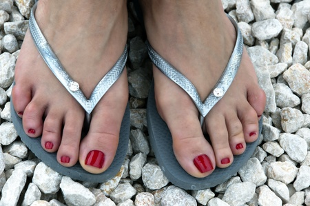 flop: feet of a caucasian woman wearing red nail-polish and flip-flops Stock Photo