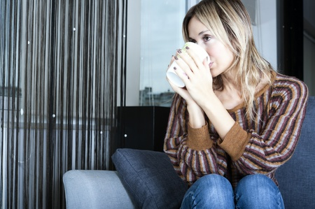 blond woman holding a beverage mug and looking through her window  photo