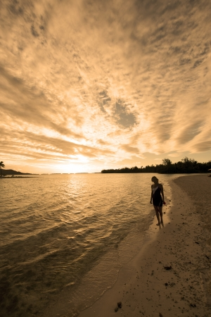 contemplates: A female in silhouette contemplates the beauty of a moody beach sunrisesunset. Stock Photo