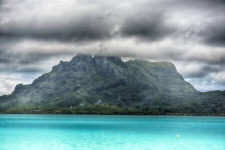 douche de tempête à l'horizon d'un motu de Bora Bora
