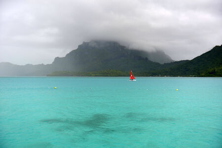 motu: Storm shower on the horizon of a motu in Bora Bora