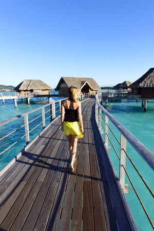 Woman at luxury resort looking at view on an over water bungalow, photo