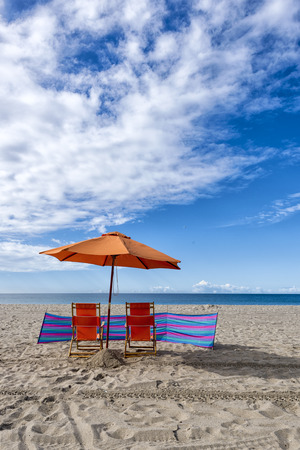 lounge chairs: Lounge Chairs and Umbrella at the Beach