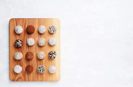 Image of energy balls prepared  with cocoa, coconut, nut ,sesame,almonds and fruits . Vegan chocolate truffles. Flat lay with copy space.