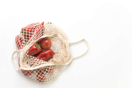 Reusable mesh string knitted shopping bag with tomatoes and red peppers. Zero Waste concept.Eco friendly.