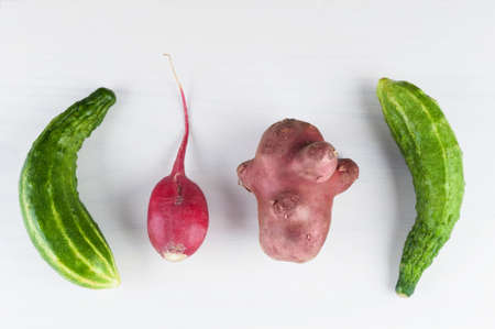 Ugly vegetables laid out in the row on a white wooden background. Ugly food concept, flat lay, horizontal orientation.