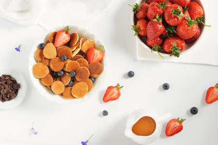 Sweet homemade bowl with tiny pancakes with chocolate,honey,strawberries  and blueberries on white table. Flat lay. Horizontal, selective focus. 版權商用圖片