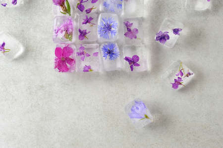 Floral ice cubes on the gray background, top view. Edible flowers frozen in ice cubes. Horizontal with space for text. 免版税图像