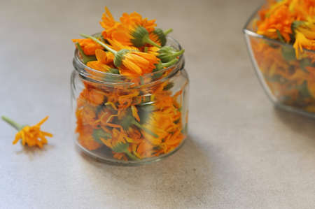 Calendula or marigold flowers in the glass jar on the gray background. Preparation flowers for drying. Selective focus ,horizontal.