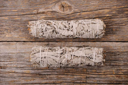 Dried white sage smudge bundles on old distressed wood background.Aroma smoke for energy clearing and healing.Close up with space for text.