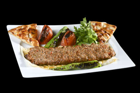 turkish kebab: Adana kebab is a long, hand-minced meat kebab mounted on a wide iron skewer and grilled on an open mangal filled with burning charcoal.