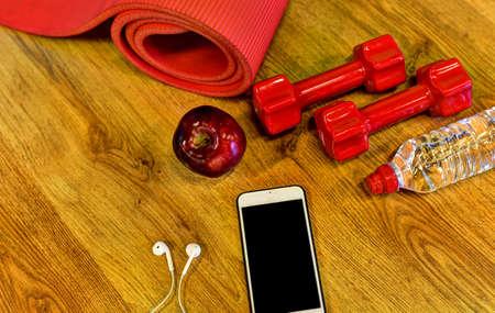Dumbbells, water bottle, smartphone, headphones and apple. Fitness concept