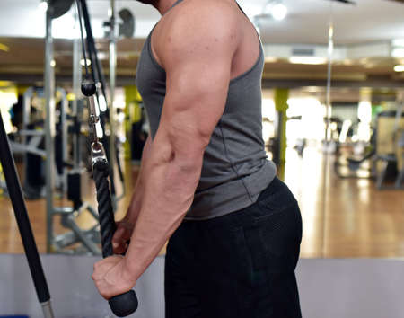 Muscular guy is training at the fitness center