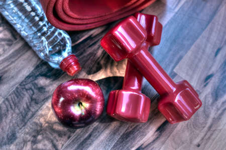 Dumbbells, water bottle and apple. Fitness concept