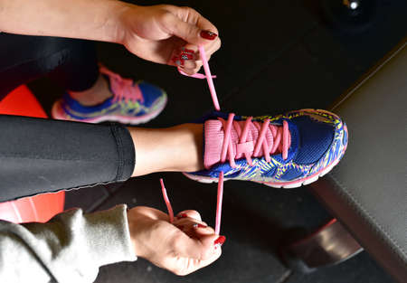 Young girl is tying her shoes for running