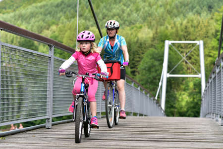 Mother and daughter riding a bike on the bicycle road from Turnov to Mala Skala, Czech Republic Editorial