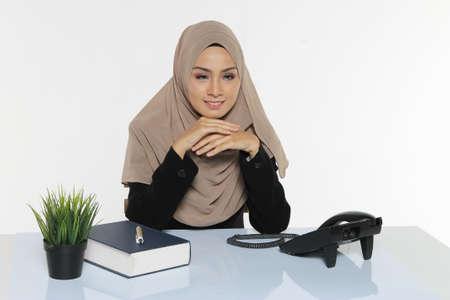 Beautiful Muslim Business woman executive wear Hijab sitting on a desk facing forward
