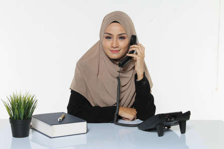 Beautiful Muslim Business woman executive wear Hijab sitting on a desk make a call with angry face reaction Stock Photo