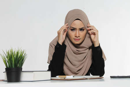 Beautiful Muslim Business woman executive wear Hijab sitting on a desk with a stress face reaction