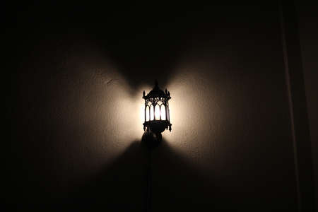oil lamp: An illuminated wall mounted islamic lamp hanging on the wall over black background Stock Photo