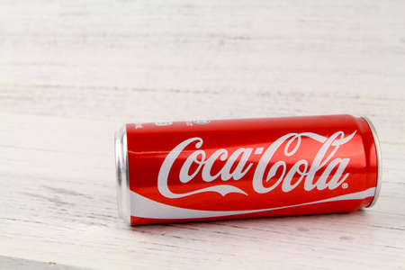 KUALA LUMPUR, MALAYSIA - 6th August 2017: A can of Coca Cola soft drinks over wooden background. Produced and manufactured by The Coca-Cola Company, an American multinational beverage corporation.