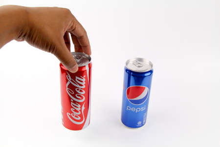cola canette: KUALA LUMPUR, MALAYSIA - 6th August 2017: Hand holding select choose coca cola over pepsi can isolated white background. Symbol of one of the greatest business rivalries of all time.