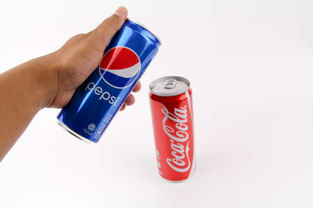 KUALA LUMPUR, MALAYSIA - 6th August 2017: Hand holding select choose pepsi over coca cola can isolated white background. Symbol of one of the greatest business rivalries of all time.