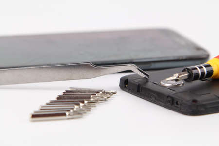dismantle: Cell phone repair. Smartphone parts and tools for recovery, selective focus.