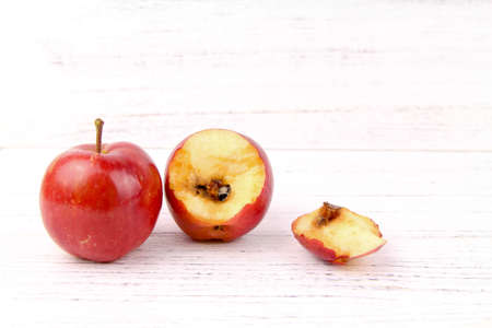A good and bitten red apple rotten from inside isolated white background