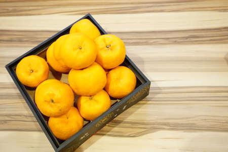 Mandarinen oder Lokam über hölzernem Hintergrund für chinesische Neujahrsfeier Standard-Bild