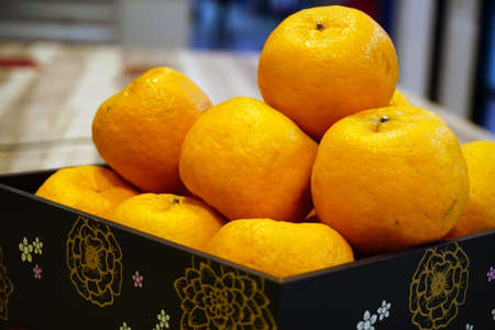 Close up Mandarin oranges or Lokam inside beautiful wooden tray for Chinese New Year celebration over wooden background. Selective Focus