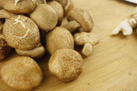 Fresh Shiitake Mushroom on wooden background. Food Preparation. Selective Focus. (Lentinula edodes)