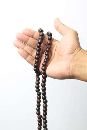 Male hand holding muslim beads rosery or tasbih over white background.