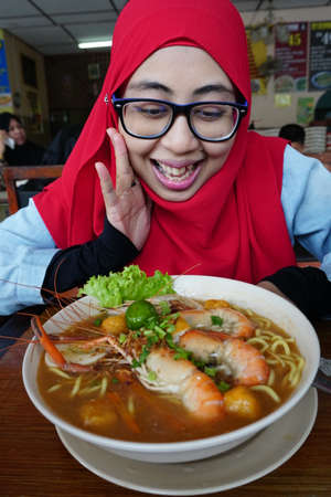 Muslim Woman enjoy eating delicious noodle or Malaysia Spicy Noodle Mee Rebus in a local restaurant.