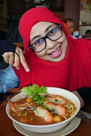 La donna musulmana si diverte a mangiare deliziosi noodle o Malaysia Spicy Noodle Mee Rebus in un ristorante locale.