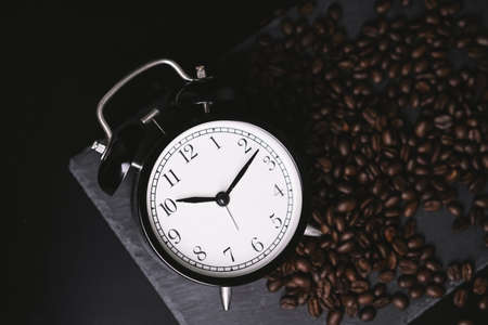 vintage alarm clock and coffee beans on slate stone plate. Selective Focus. Copy Space Concept