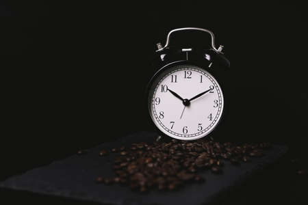 vintage alarm clock and coffee beans on slate stone plate. Seletive Focus. Copy Space concept. Celebrate International Coffee Day On October