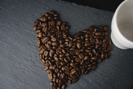 Coffee bean love shape on a slate. Celebrating International Coffee Day on October.