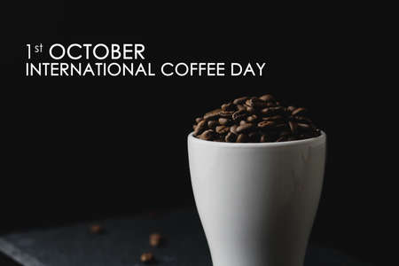 Closeup Coffee Bean on a white cup over dark black background with word 1st October International Coffee Day Celebration. Copy Space Concept Stock fotó