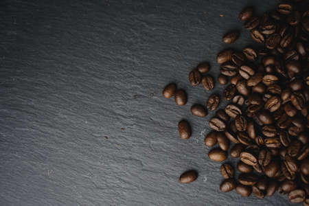 Close up Coffee beans on a slate texture. Isolated dark background. Celebrate international Coffee Day